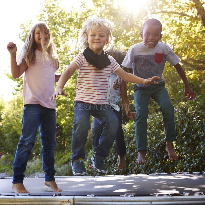 Quattro bambini divertendosi insieme su un trampolino nel giardino immagini stock