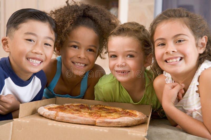Quattro bambini in giovane età all'interno con sorridere della pizza fotografia stock libera da diritti