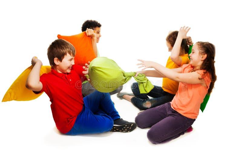 Quattro bambini che hanno lotta di cuscino fotografia stock