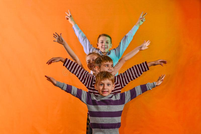 Quattro bambini stanno in una fila e sollevano le loro mani ai lati sull'età di un fondo giallo, quei più giovani guardano fuori  fotografia stock libera da diritti