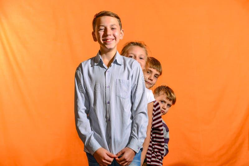 Quattro bambini stanno in una fila su un fondo giallo, quei più giovani guardano fuori per quei più vecchi immagine stock