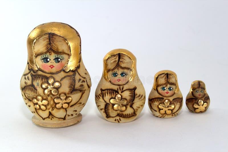 Quattro bambole annidate di legno su un primo piano bianco del fondo fotografie stock libere da diritti