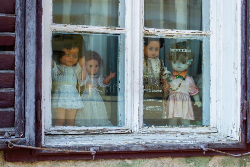Quattro bambole terrificanti vestite in vestiti rumeni bianchi e con tradizionali, visualizzati in una finestra, mentre esaminand immagine stock