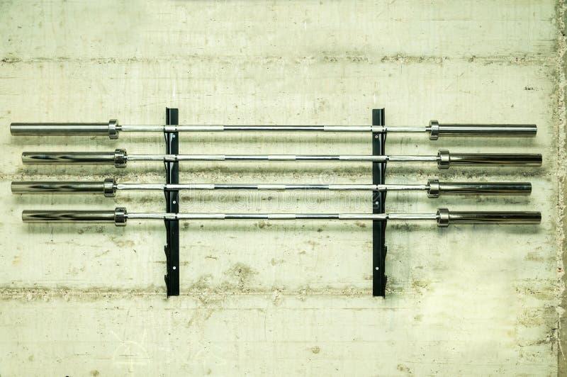 Quattro barre del peso del bilanciere sul supporto avvitato sulla parete di lerciume hanno preparato per lo sport di sollevamento immagini stock libere da diritti