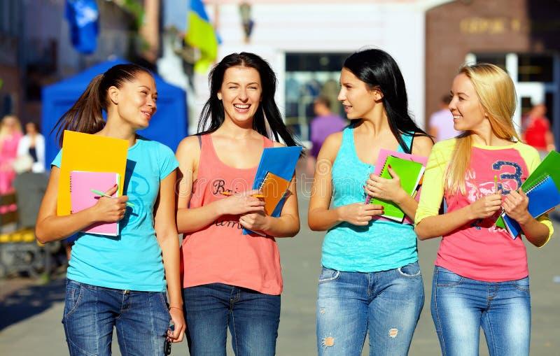 Quattro belle ragazze di istituto universitario che camminano sulla via fotografia stock libera da diritti