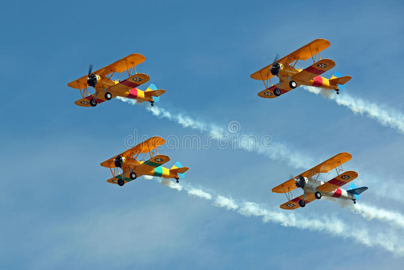 Quattro biplani che volano nella formazione con fumo immagine stock