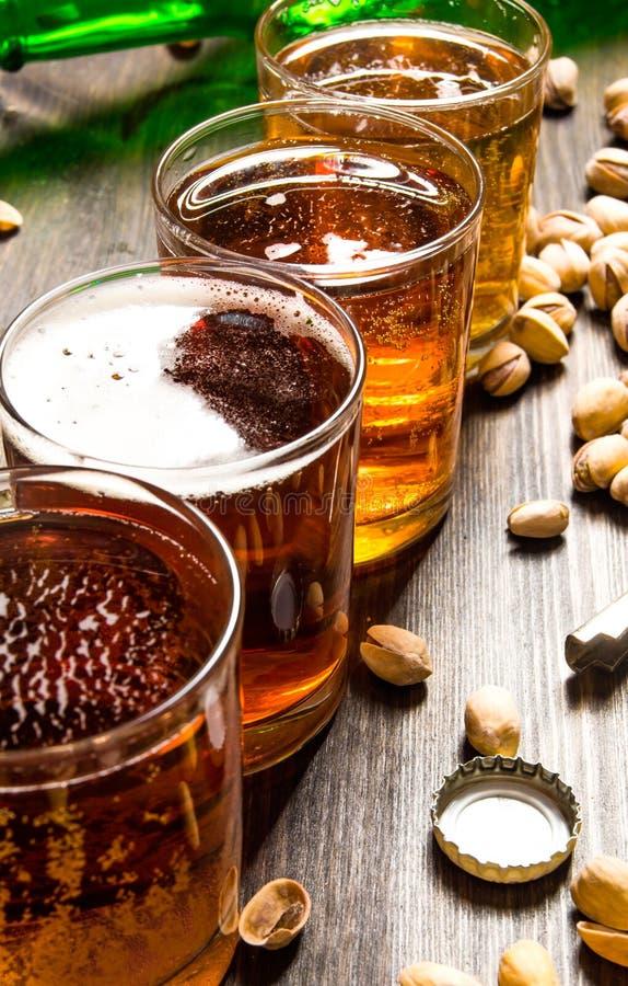 Quattro birre con i pistacchi su una tavola di legno fotografia stock libera da diritti