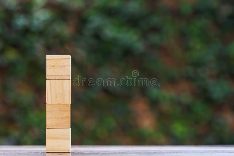 Quattro blocchi di legno vuoto impilato sulla tavola di legno con il fondo verde della natura e spazio a giusto uso per input il  immagine stock libera da diritti