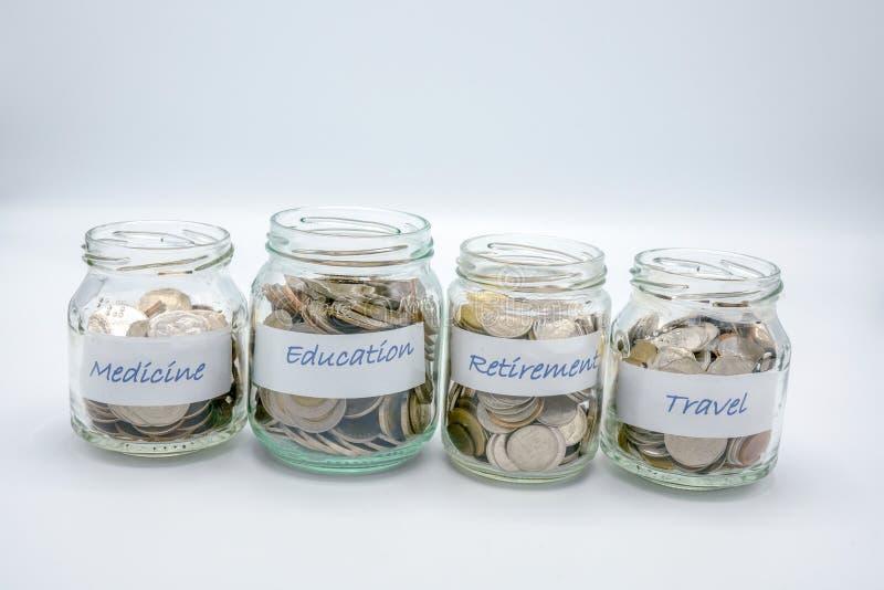Quattro bottiglie di vetro hanno riempito di monete con la carta di etichetta di medicina, l'istruzione, il pensionamento, viaggi immagini stock libere da diritti