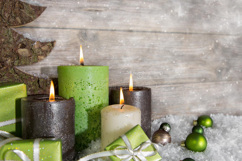 Quattro candele brucianti di arrivo in verde ed in marrone sul backgro di legno fotografia stock