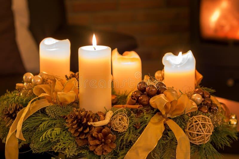 Quattro candele di arrivo su una corona immagine stock