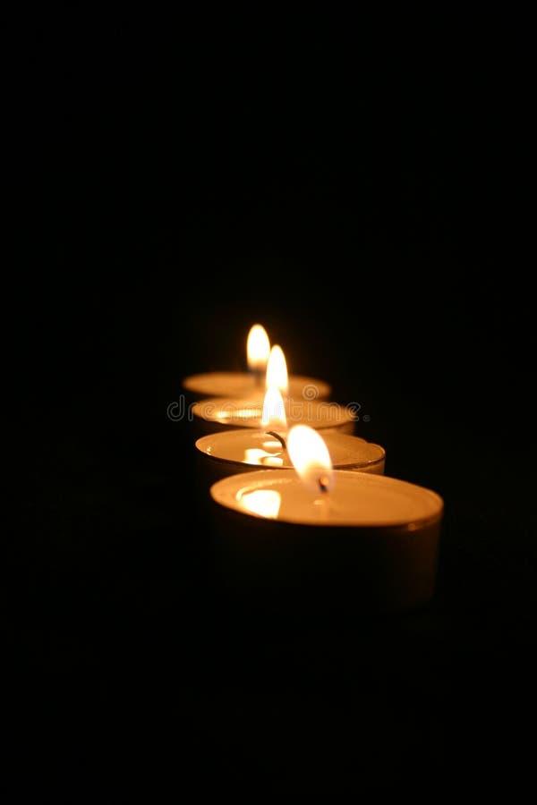 Quattro candele nello scuro immagine stock libera da diritti