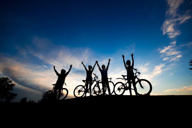 Quattro ciclisti con le mani sollevate al tramonto fotografie stock