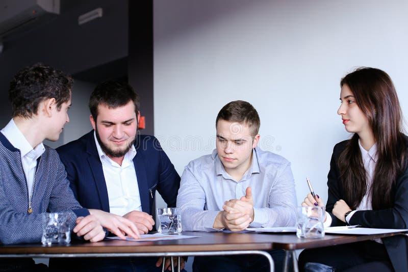 Quattro colleghi dell'uomo e della donna si riuniscono per la riunione all'ufficio di immagine stock