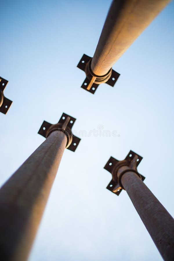Quattro colonne metalliche che indicano la manifestazione del cielo da sotto fotografie stock