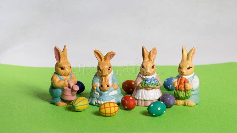 Quattro coniglietti di pasqua ` s del bambino con le uova sul prato verde immagine stock libera da diritti