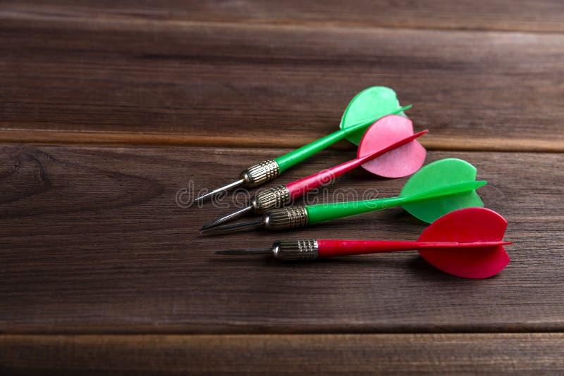 Quattro dardi colorati su un fondo di legno Colpisca l'obiettivo fotografie stock libere da diritti