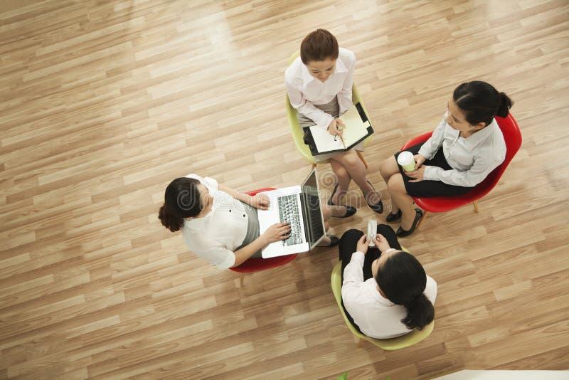 Quattro donne di affari che lavorano al progetto che si siede in un cerchio, colpo sopraelevato fotografie stock