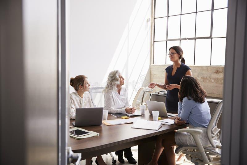 Quattro donne di affari nella riunione, veduta dalla entrata fotografia stock