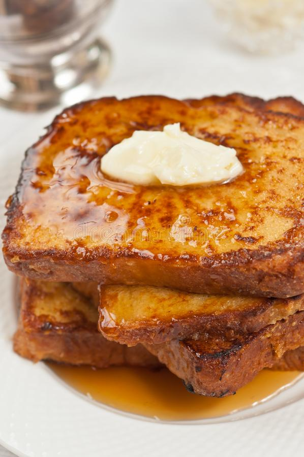 Quattro fette di pane tostato francese di recente cotto e casalingo con burro e di sciroppo d'acero immagini stock libere da diritti