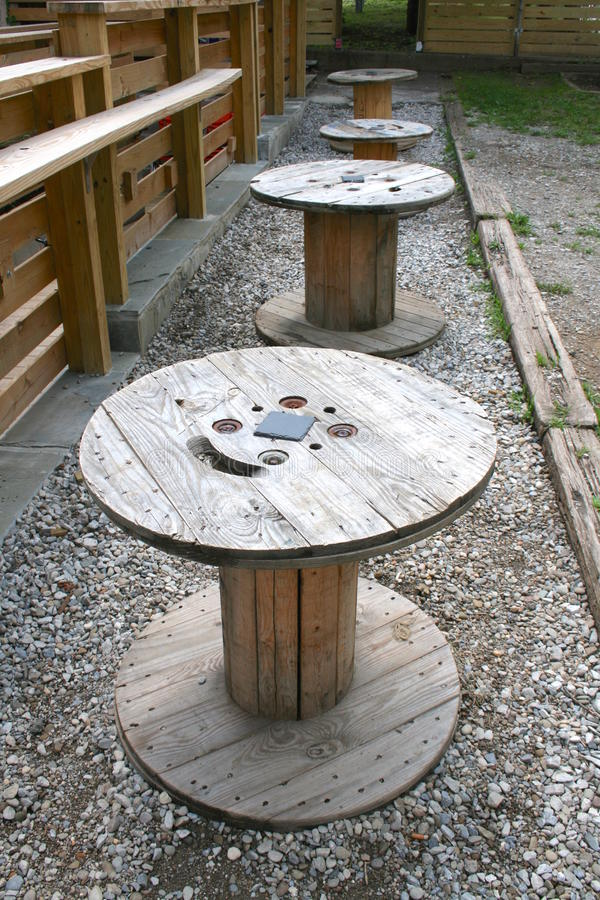 Quattro fusi di legno del cavo in una fila come Tabelle sulle rocce immagini stock libere da diritti