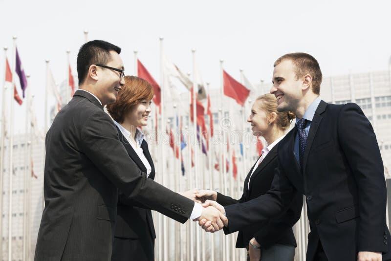 Quattro genti di affari sorridenti che incontrano e che stringono le mani all'aperto, Pechino fotografia stock