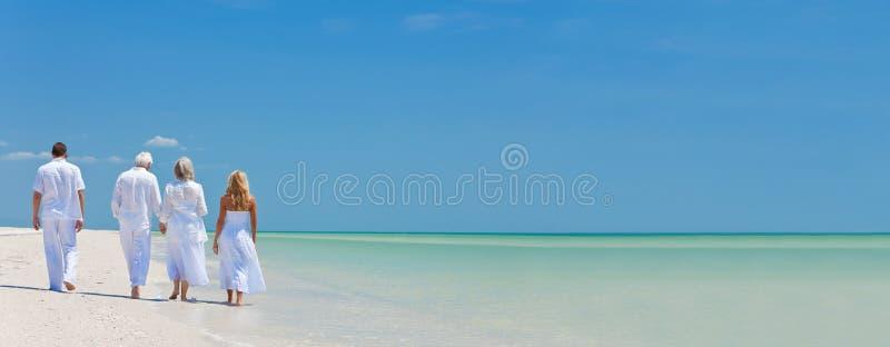 Quattro genti, due anziani, coppie della famiglia, camminanti su tropicale sono fotografia stock