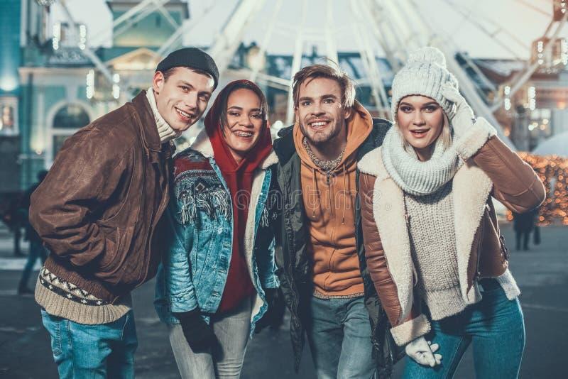 Quattro genti sorridenti che posano per la foto all'aperto in vestiti caldi fotografia stock