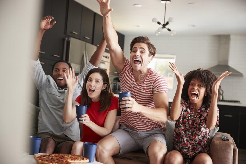 Quattro giovani amici adulti che guardano gli sport sulla celebrazione della TV fotografia stock