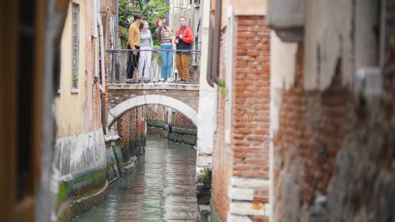 Quattro giovani amici che stanno sul ponte fra due costruzioni sopra il canale idrico - Venezia, Italia fotografia stock