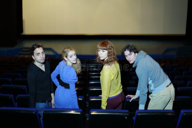 Quattro giovani amici si siedono sui sedili nel corridoio del teatro del cinema fotografia stock libera da diritti
