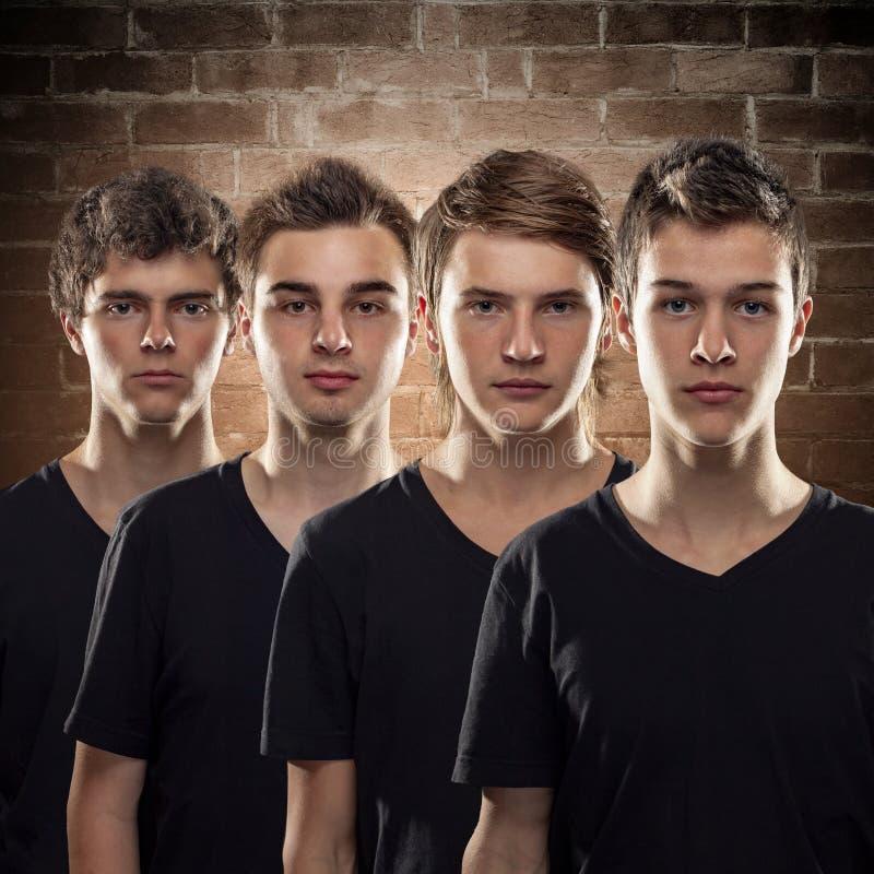 Quattro giovani amici stanno accanto a ogni altro nell'unità fotografia stock libera da diritti