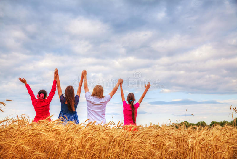 Quattro giovani che restano con le mani sollevate fotografia stock libera da diritti