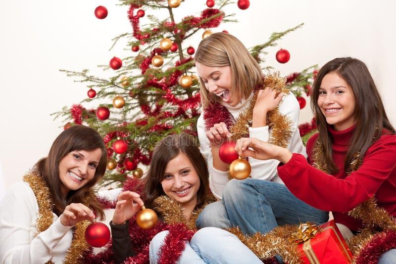 Quattro giovani donne che hanno divertimento su natale immagini stock