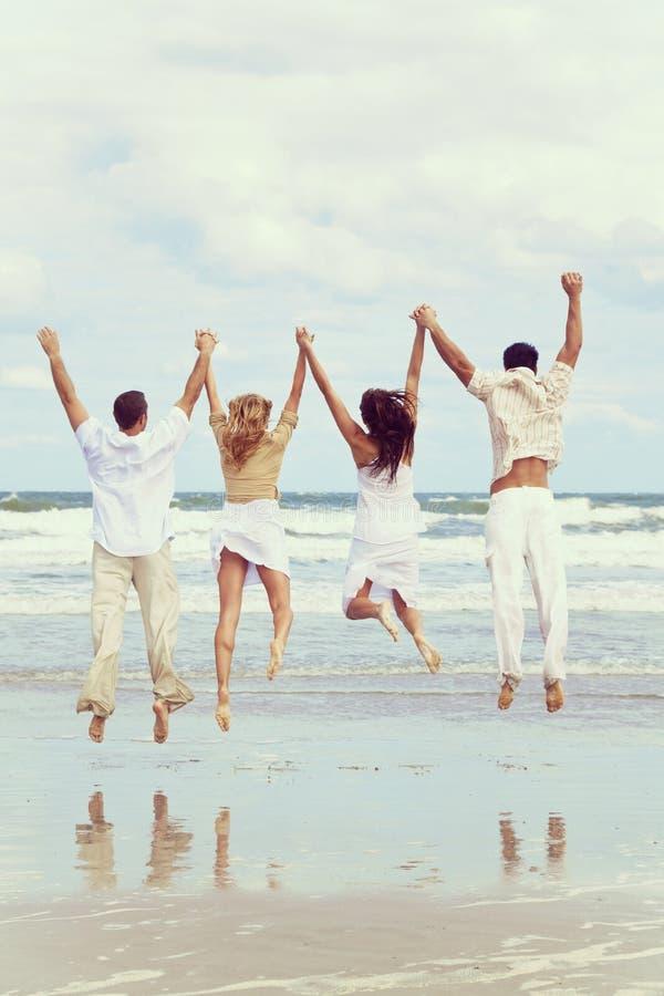 Quattro giovani due coppie che saltano nella celebrazione sulla spiaggia immagini stock