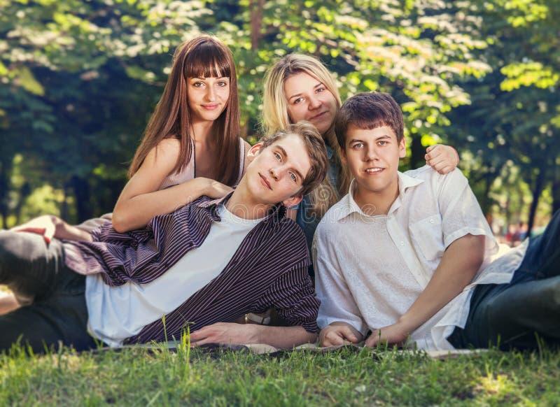 Quattro giovani sul prato inglese verde in parco immagini stock libere da diritti