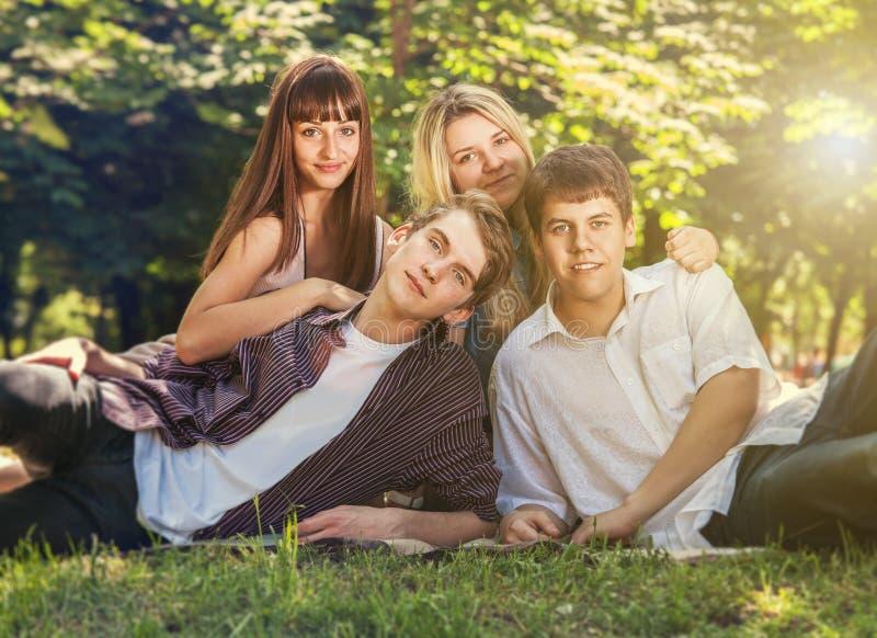 Quattro giovani sul prato inglese verde in parco immagine stock libera da diritti
