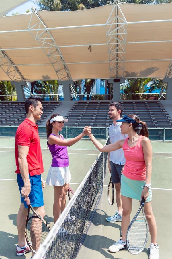 Quattro giovani tennis che mettono le mani prima dell'doppi abbinano insieme fotografia stock