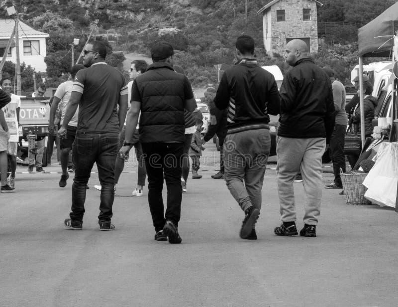 Quattro giovani uomini colorati d'avanguardia che camminano a partire dalla macchina fotografica godono di un festival del villag fotografia stock