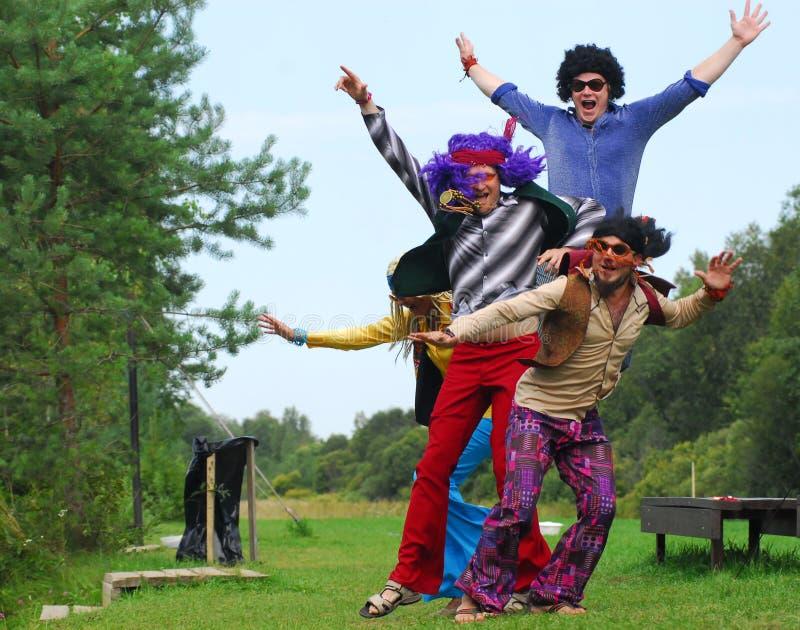 Quattro hippy che saltano in su immagine stock
