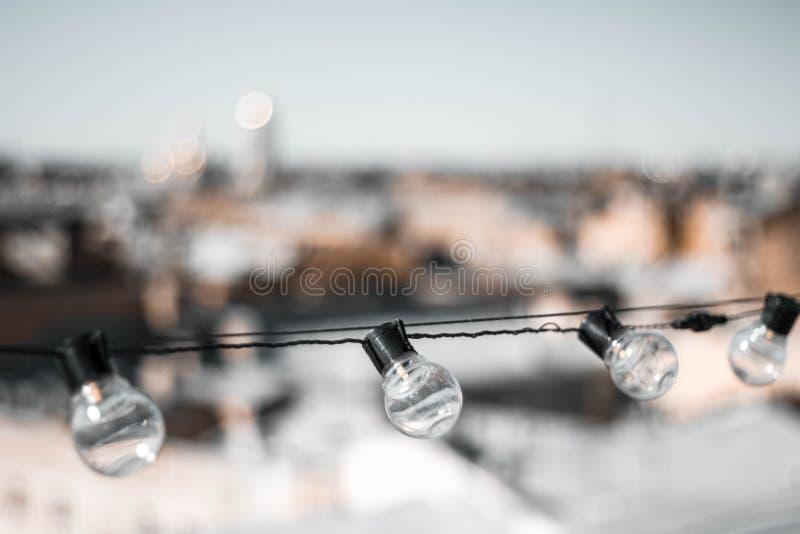 Quattro lampadine di vetro contro i tetti delle case e del cielo La lampadina sulla cima La vista dalla parte superiore Fine in s fotografie stock