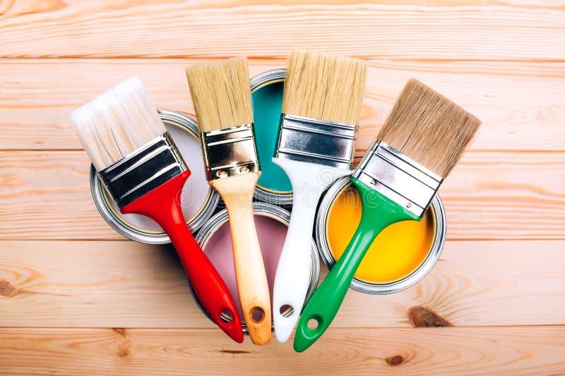 Quattro latte aperte di pittura con le spazzole su loro su sfondo naturale di legno fotografia stock libera da diritti