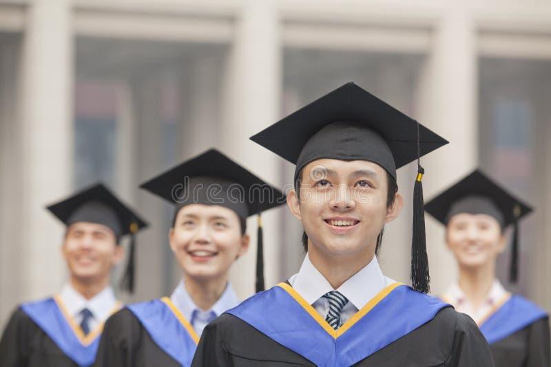 Quattro laureati sorridenti dell'università negli abiti e nei tocchi di graduazione, cercare immagine stock