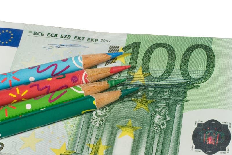 Quattro matite di colore su un'euro fattura immagini stock