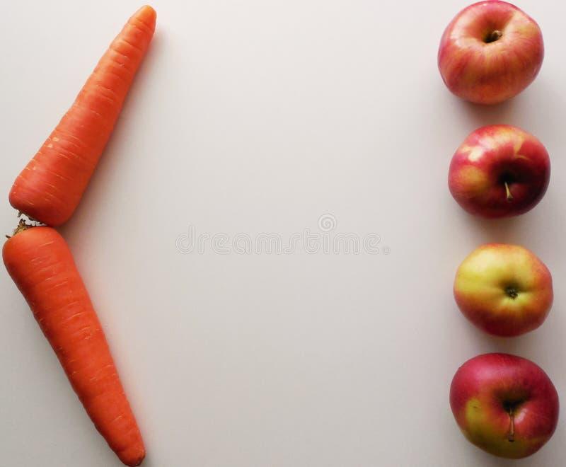 Quattro mele e due carote su un fondo bianco immagine stock