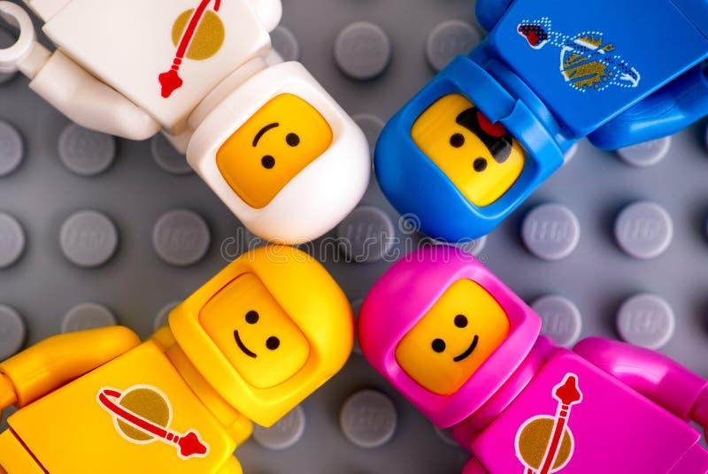 Quattro minifigures dell'astronauta di Lego sul fondo grigio della piastra di base fotografia stock libera da diritti