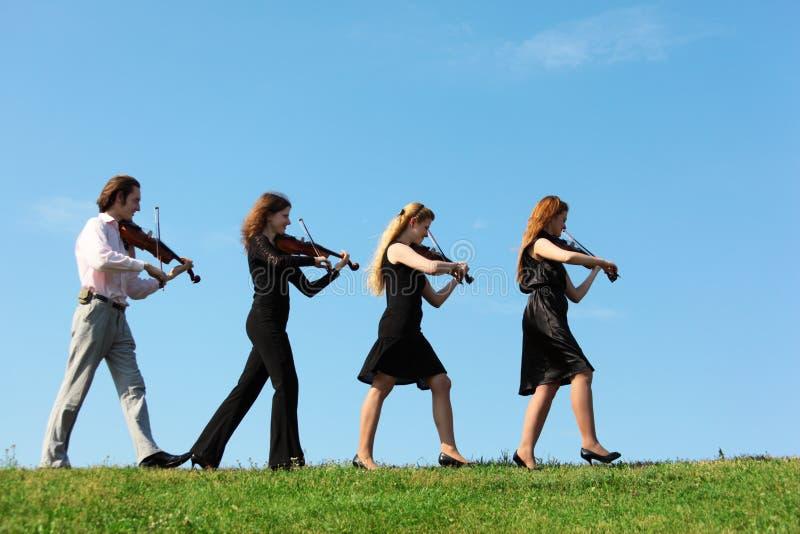 Quattro musicisti vanno giocare i violini contro il cielo fotografia stock