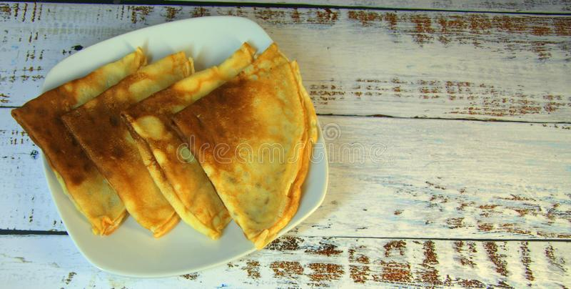 Quattro pancake freschi su una bugia ceramica del piatto su una tavola di legno fotografie stock