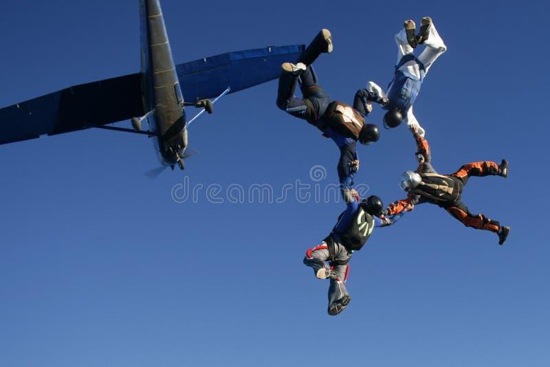 Quattro paracadutisti saltano dall'aereo fotografie stock