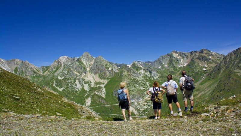 Quattro persone che guardano intorno su una montagna immagini stock libere da diritti